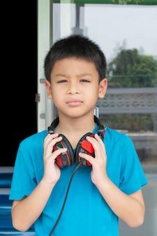 Мальчик руки азиатский держа наушники на предпосылке шеи расплывчатой.