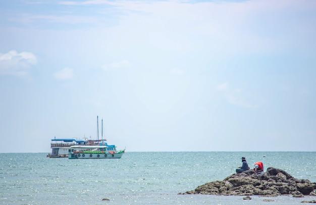 岩や海のボートで釣りをする漁師