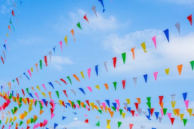 多色のパーティーの虹の旗を祝うために青空に