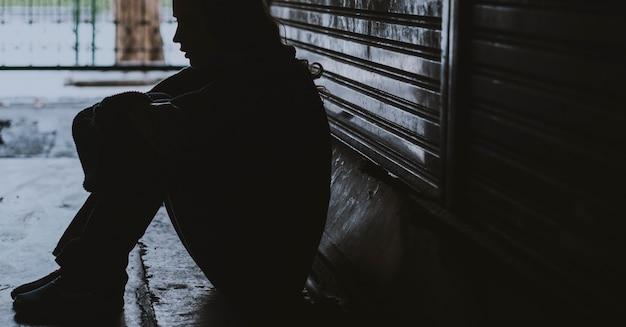 Бездомная женщина сидит на уличной стороне безнадежная