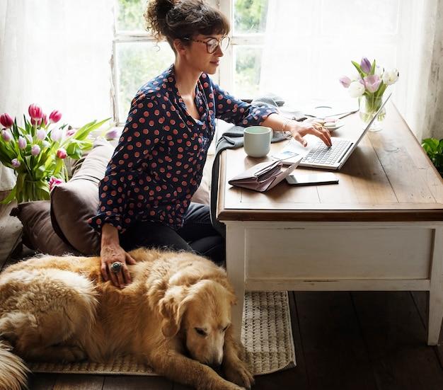 彼女の犬と家で働く女性