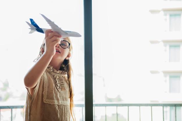 Маленькая девочка, играющая с игрушечным самолетом