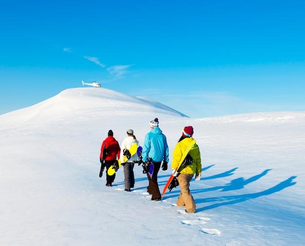 美しい冬の朝を楽しむスノーボーダーのグループ。