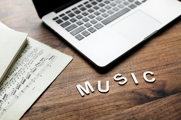Вид с воздуха на компьютерный ноутбук на деревянном столе и буквы, образующие слово музыка