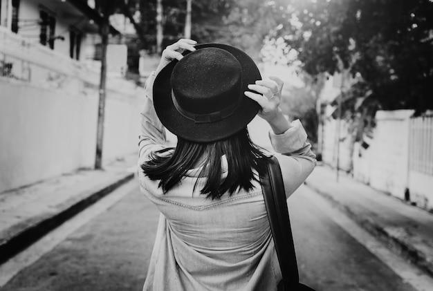 通りのグレースケールに沿って歩いているアジア人女性のリアビュー