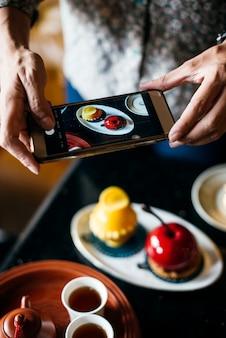 彼女の食べ物の写真を撮っている女性