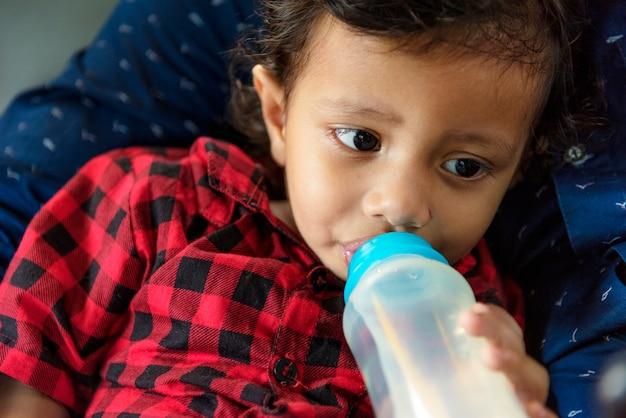 ボトルから牛乳を飲む若いインド人の少年