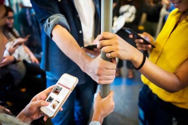 地下鉄でスマートフォンを使用する若い大人の友人のグループ