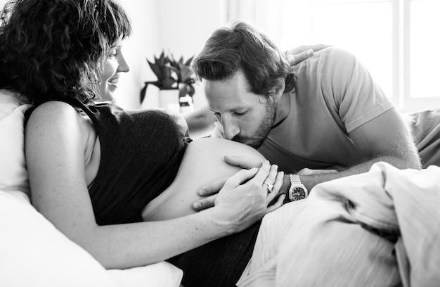 赤ちゃんのバンプにキスする夫