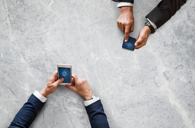 Деловые люди, синхронизирующие данные по мобильному телефону