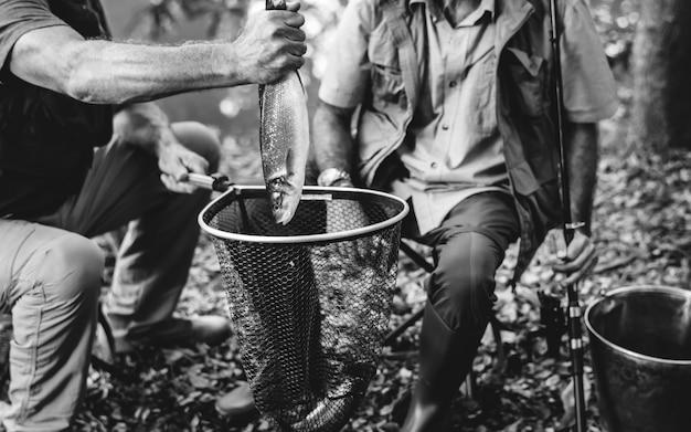 新鮮な魚を釣った成熟した男