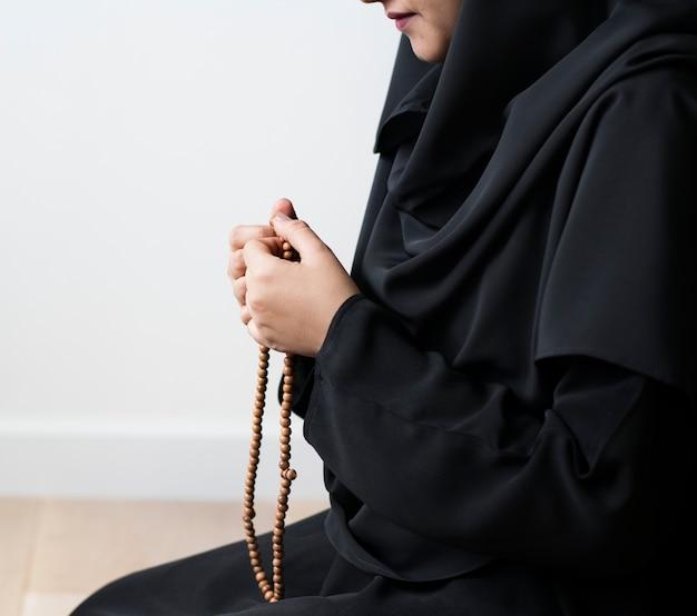 ムスリムの女性がミスバハを使ってタスビで数える