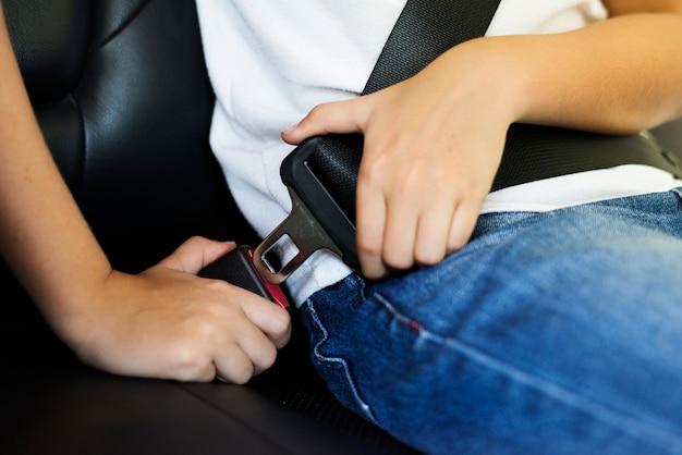 彼のシートベルトを締める少年