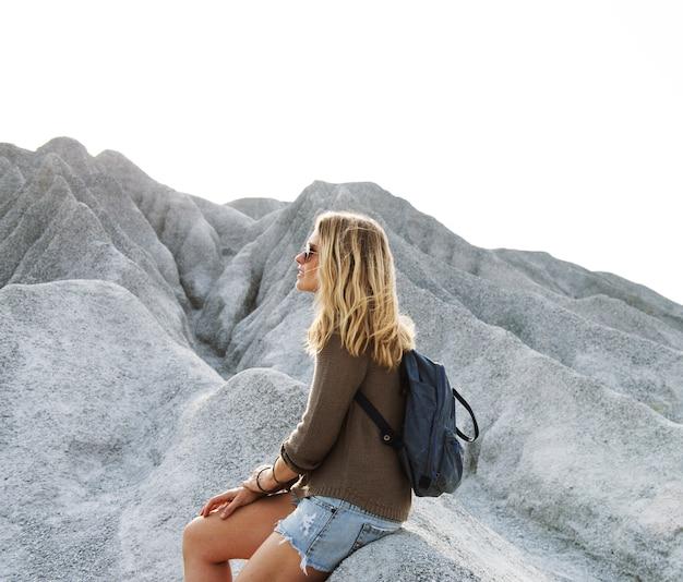 女は岩の上をハイキングして休息を取る