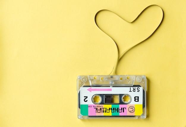黄色の背景に隔離された心臓シンボルカセットテープ