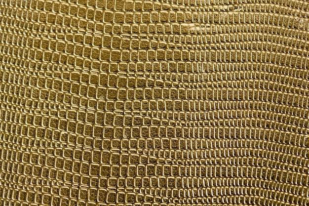 黄金の鱗状のテクスチャパターンの背景の拡大