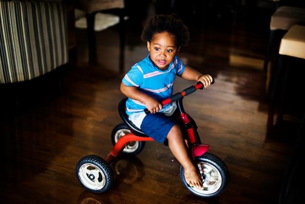 Черный ребенок едет на велосипеде в доме