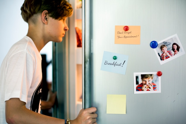 若い白人の男の子が食べ物を探して冷蔵庫を開く