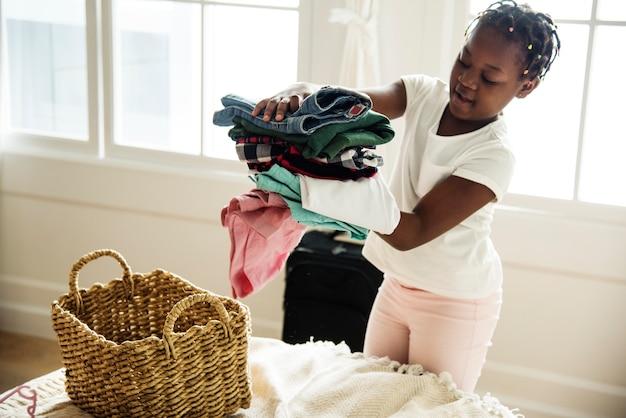 Молодая девушка-подросток помогает с складыванием одежды