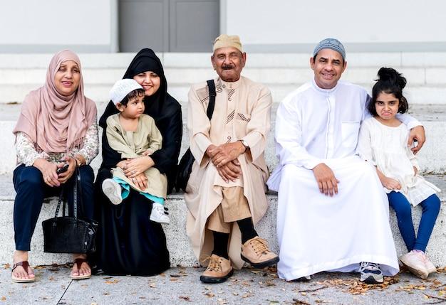 屋外で一緒に座るイスラム教徒の家族