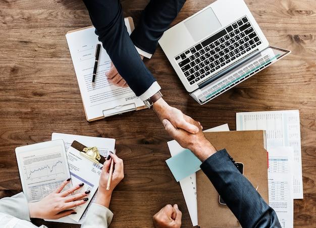 一緒に握手するビジネス人々