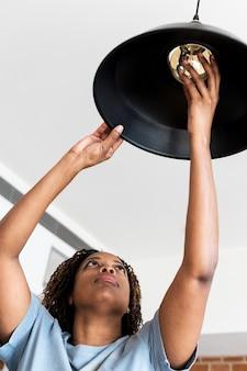 Женщина меняет лампочку