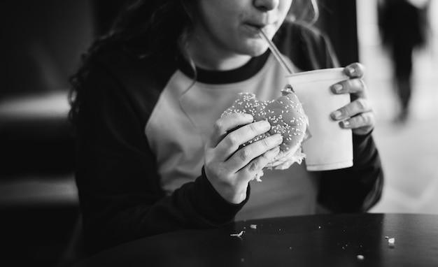 Крупный план девочка-подросток едят гамбургер концепции ожирения