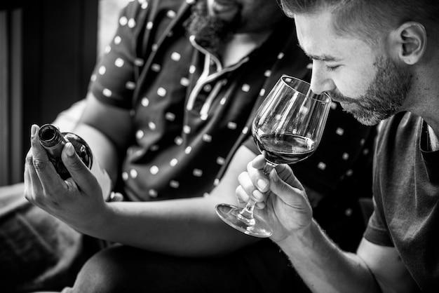 友人と赤ワインを試飲する男