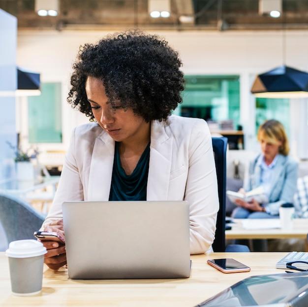 Женщина играет на своем телефоне на работе