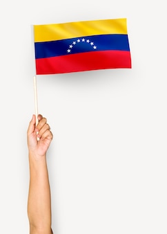 Человек, размахивающий флагом боливарианской республики венесуэла