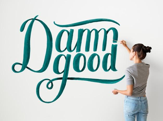 壁に引用符を書く女性アーティスト