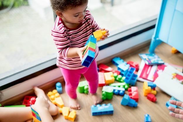 Маленькая девочка играет со строительными блоками