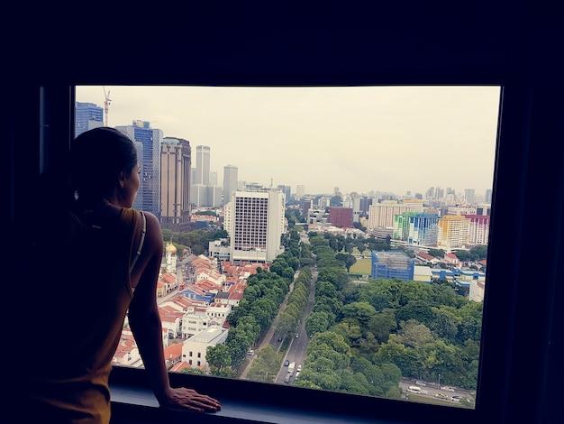 女の子、窓、都市、町の木を見て