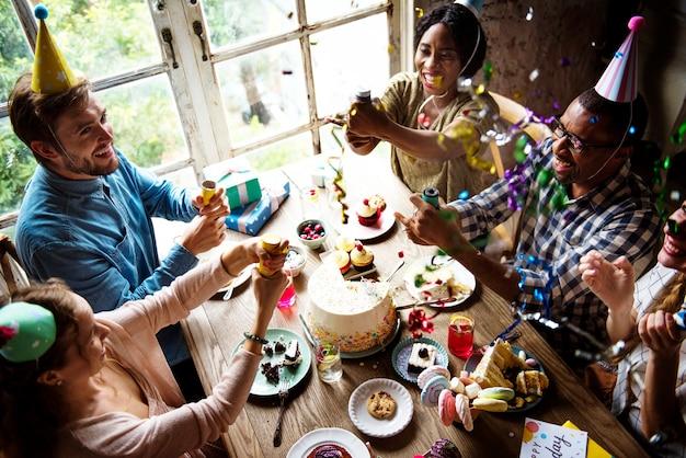 誕生日のお祝いでパーティーポッパーを使用している人々
