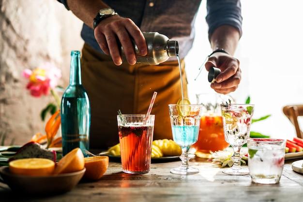 Бармен смешивает разноцветные коктейли