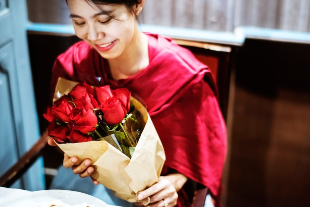女は赤いバラの花束を手に入れた