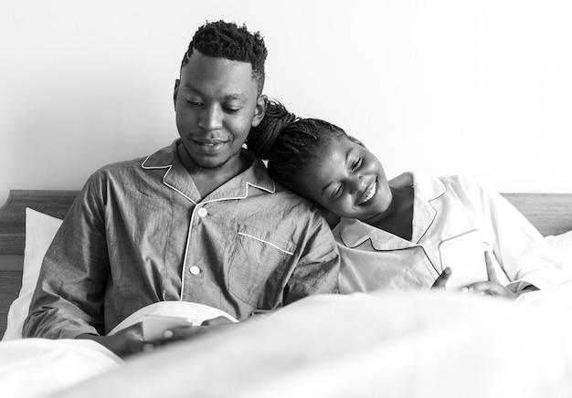 ベッドで携帯電話を使う幸せな夫婦