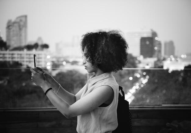 都市景観で写真を撮っている若い女性