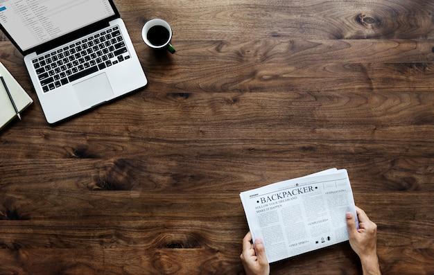 木製のテーブル上の新聞とコンピュータのラップトップを読んでいる女性の航空写真