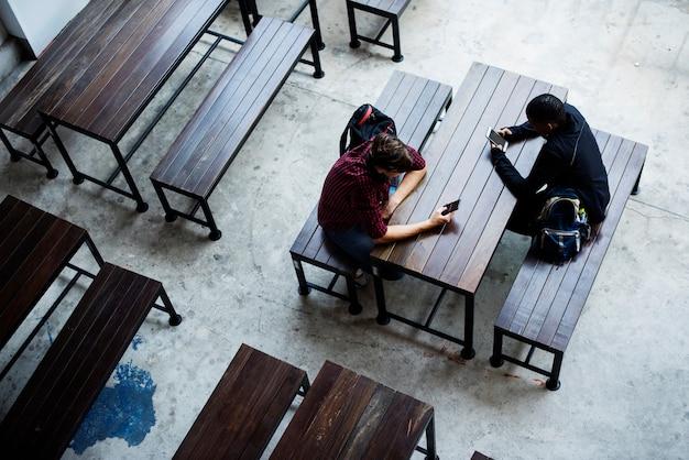 空の食堂に一緒に座っている十代の少年