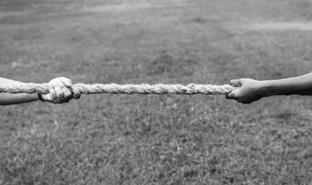戦争ゲームの綱引きでロープを引っ張る手の拡大