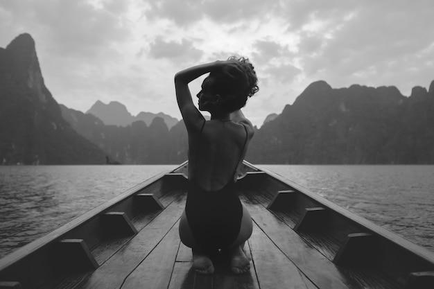 美しい女性がボートにポーズをとる