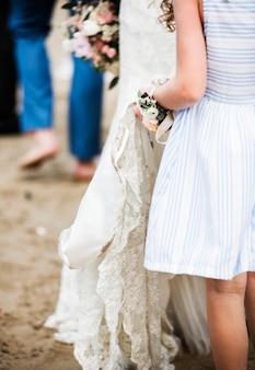 花嫁のウェディングドレスを保持するフラワーガール