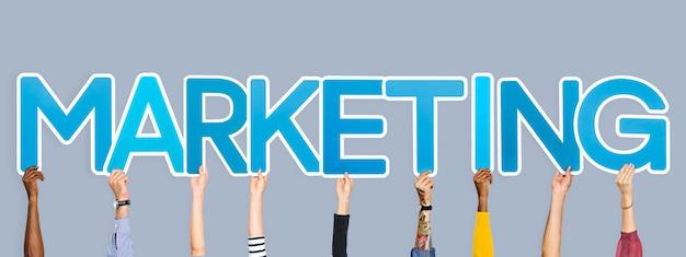 Руки, удерживающие синие буквы, формирующие слово маркетинг