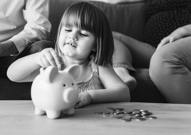 Семья, экономящая деньги в копилке