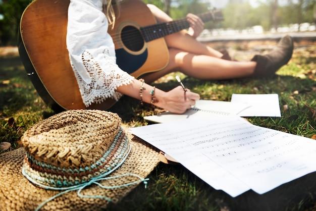 公園で音楽を作って座っている女性ギタリストの拡大写真