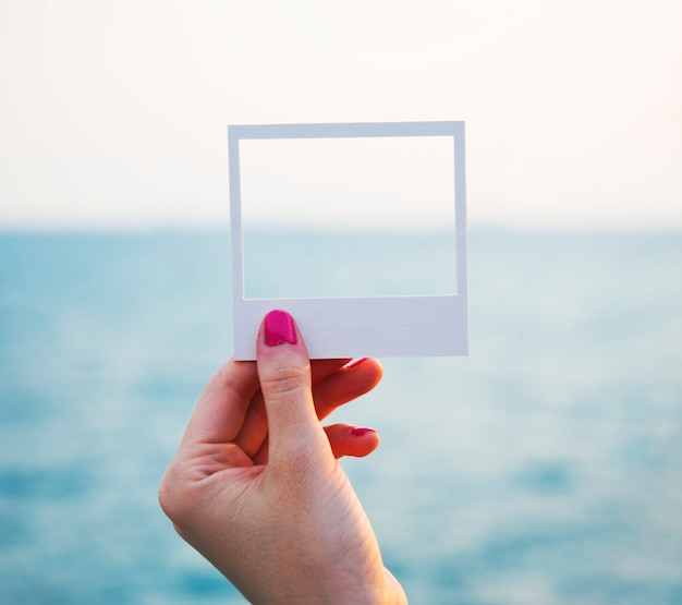 海の背景と穴の開いた紙のフレームを保持する手