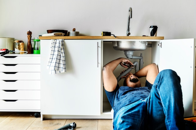 Водопроводчик, устанавливающий кухонную раковину