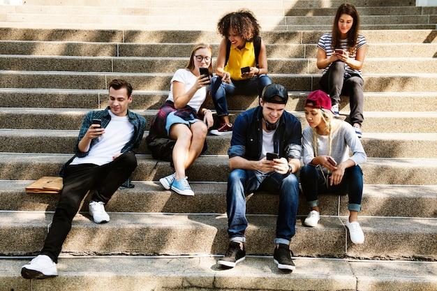 Друзья сидят на лестнице, используя смартфоны вместе и охлаждая
