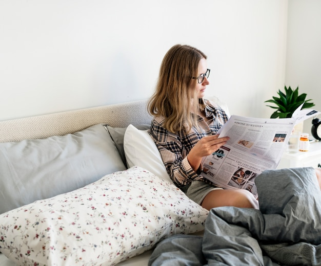ベッドで新聞を読む白人女性